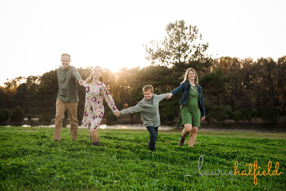 mom, dad, son, and daughter running in field | Mobile AL family photographer