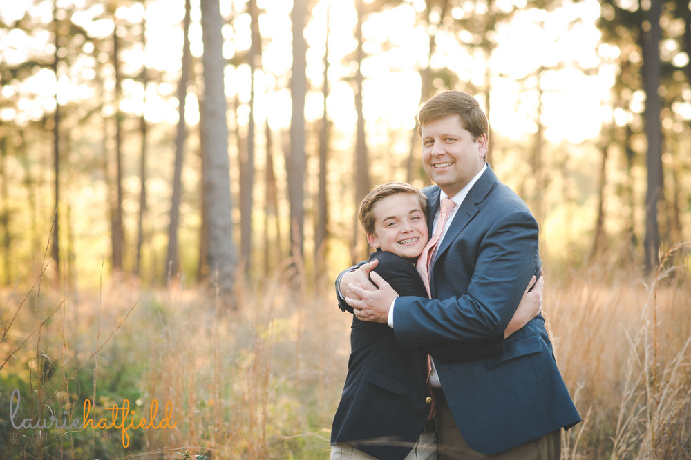 dad hugging son in field | Saraland AL family photographer