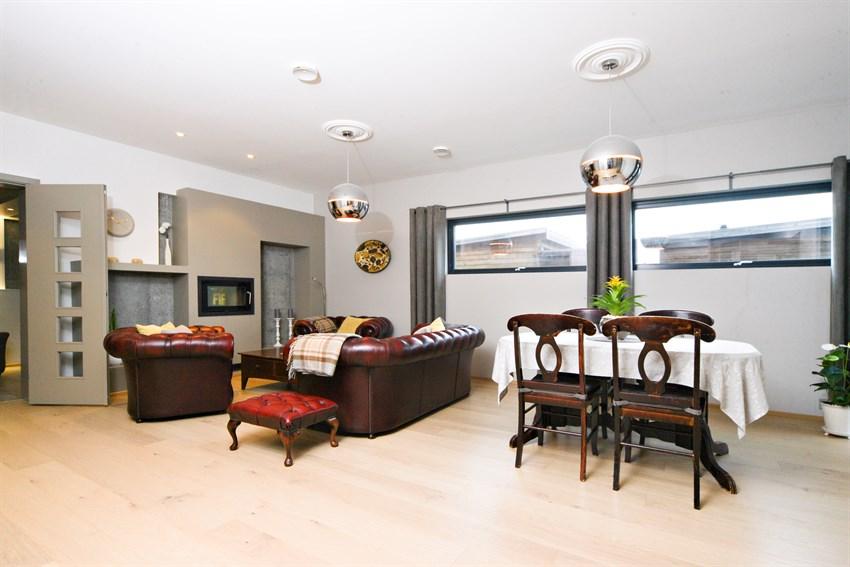Det er god plass til sofagruppe og spiseplass i hovedstuen. Flotte detaljer med stilfulle rosetter i tak.