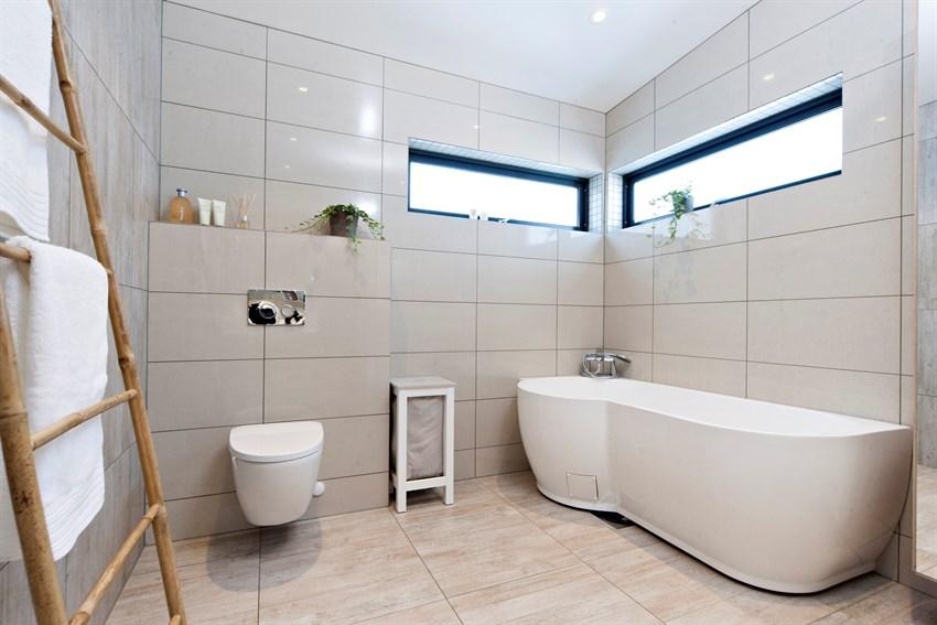 Innredet med en stor dusjnisje, badekar, vegghengt toalett, heldekkende servant med oppbevaringsmøblement.