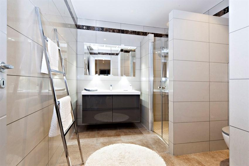 Lyst og delikat bad med flislagte gulv og vegger i underetasjen.