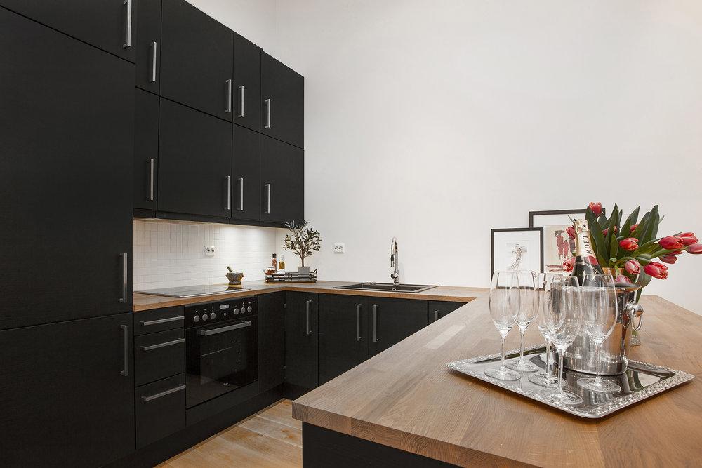 Stilrent kjøkken med matte fronter og heltre benkeplate. Integrerte hvitevarer