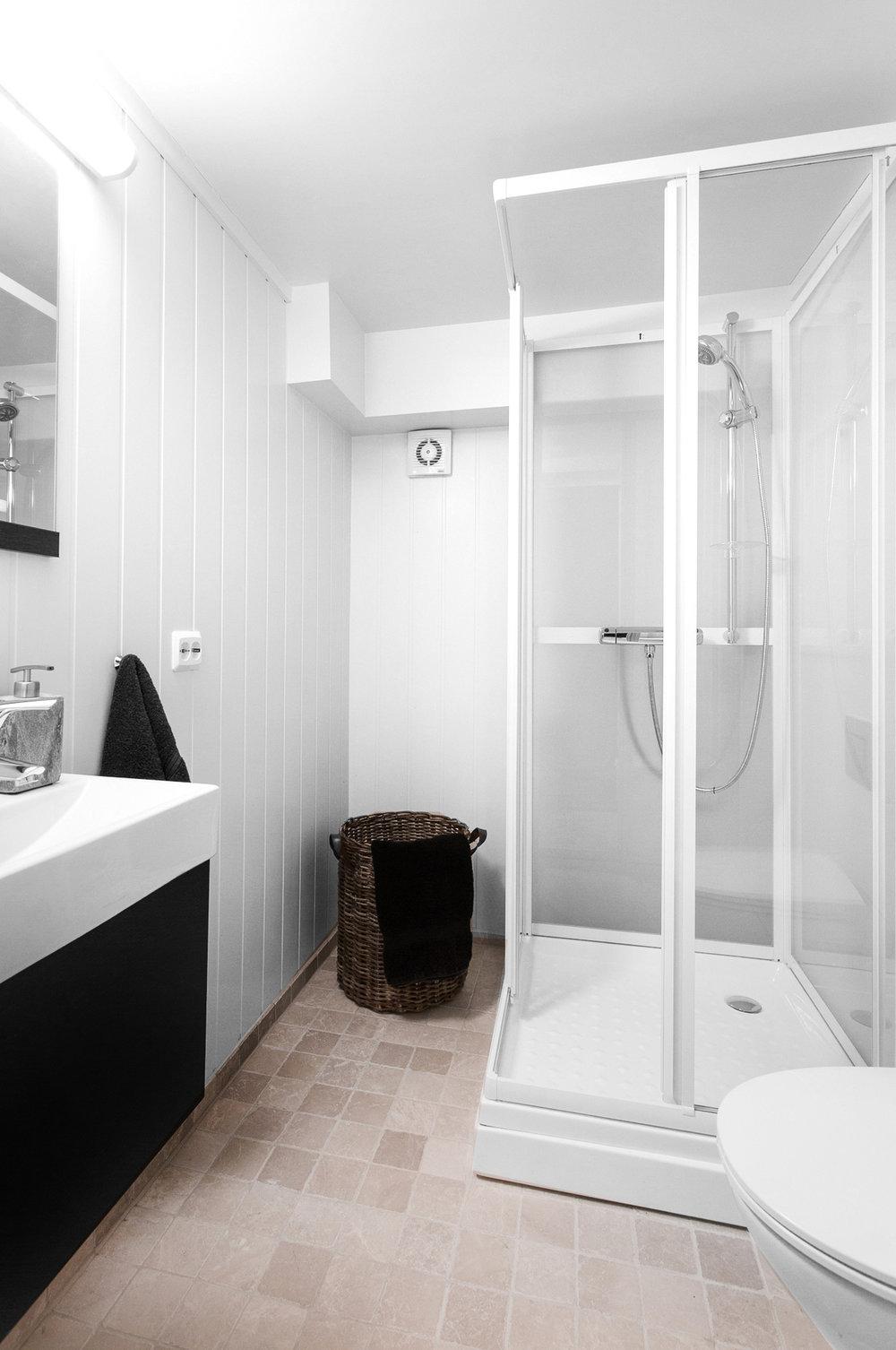 Lekkert bad i utleiedel. Fliser på gulv og malt panel på vegg. Opplegg for vaskemaskin.