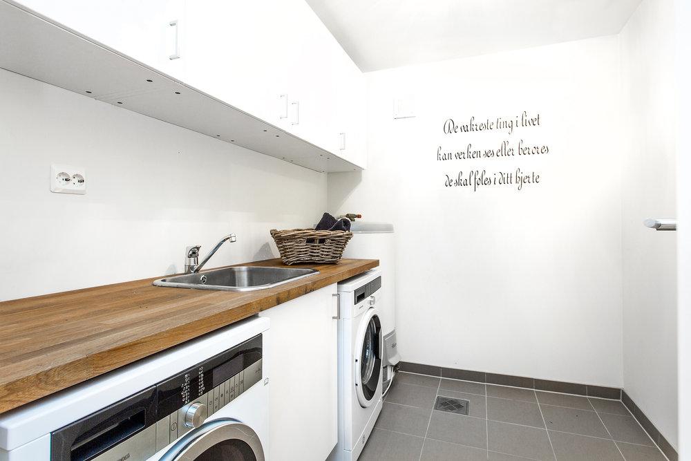 Eget vaskerom med stor og god arbeidsplass og god skapplass. Plass til vaskemaskin og tørketrommel under arbeidsbenken.