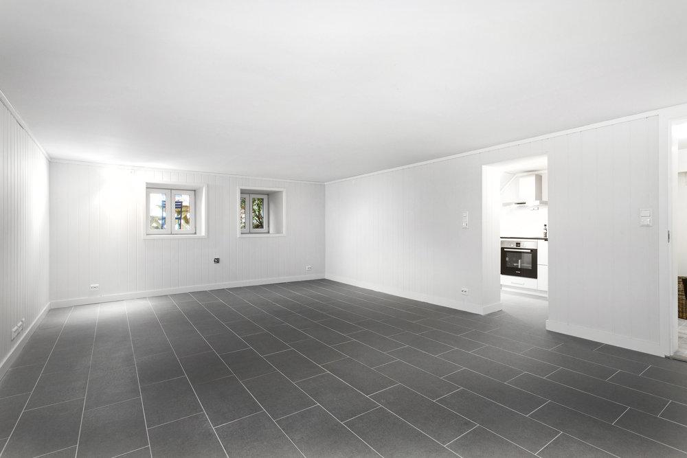 Stort og romslig oppholdsrom/soverom i utleiedel. Fliser med varmekabler i gulvet, malt himling og malt panel på vegg.
