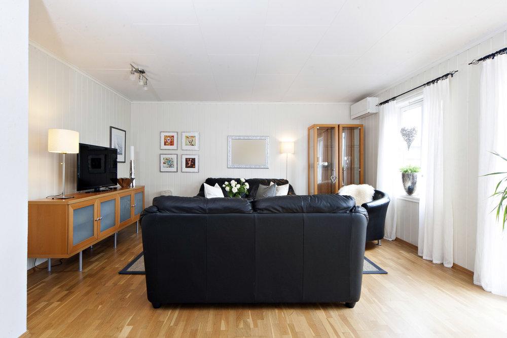 Lys og innbydende stue med plass til både sittegruppe og spisebord.