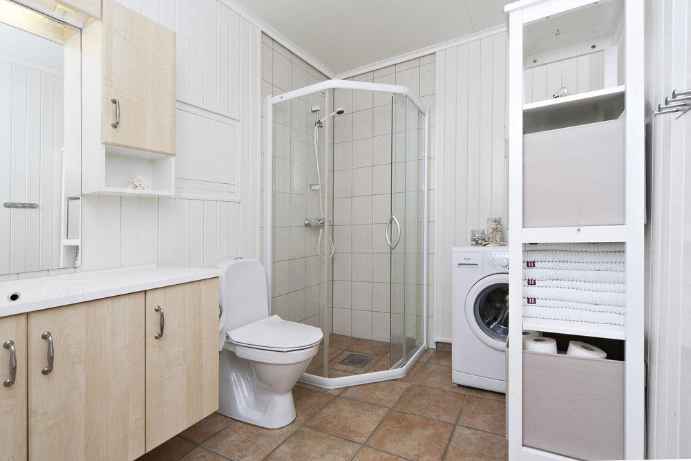 Badet har fliser på gulv og malte panelplater på vegg.