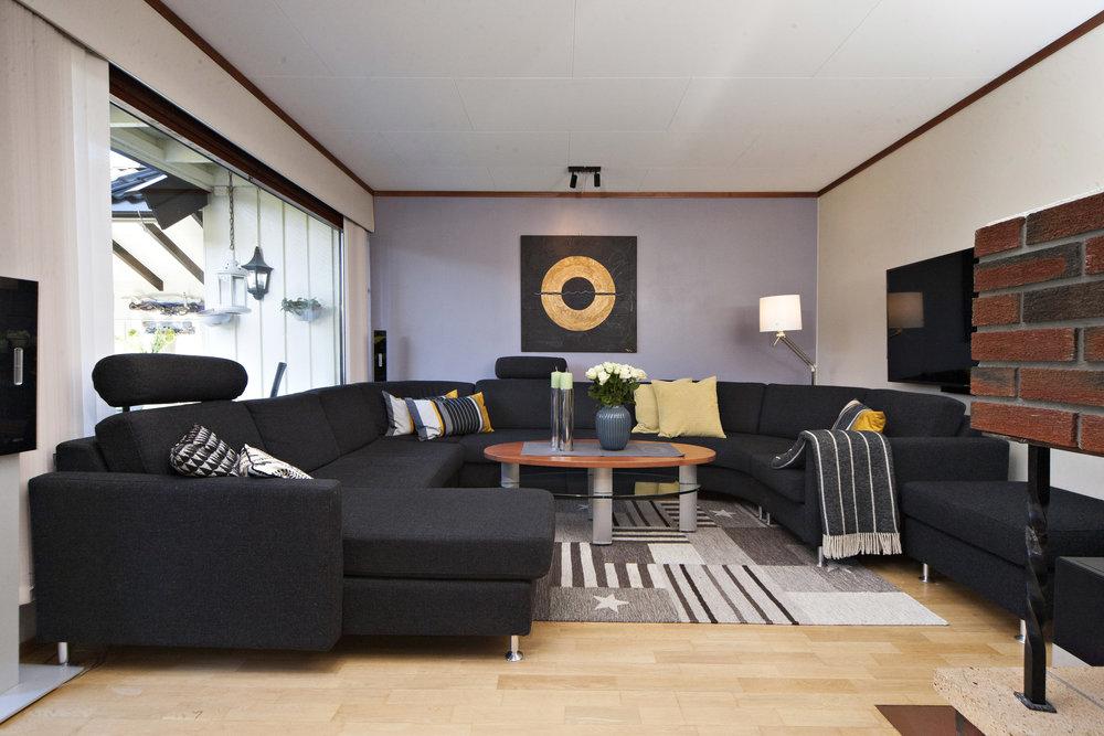 Stor og innbydende stue med romslig krok til sofa og TV.