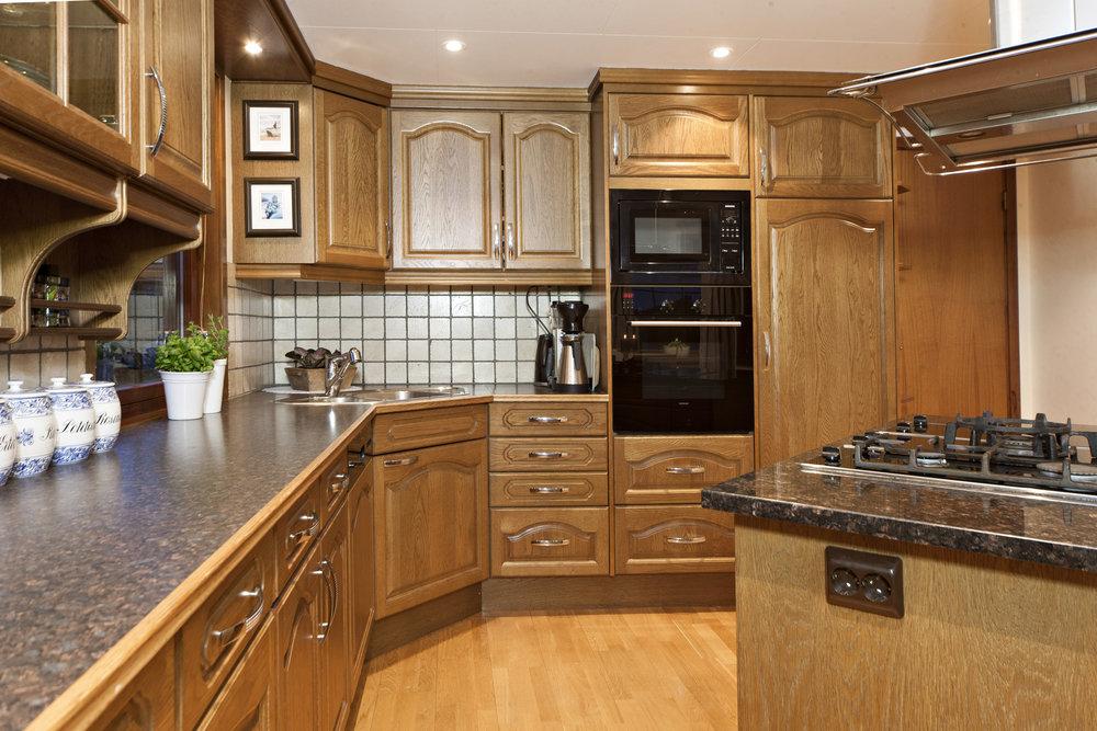 Stort og innholdsrikt kjøkken med takhøy innredning i heltre eik fra Vårt Kjøkken.