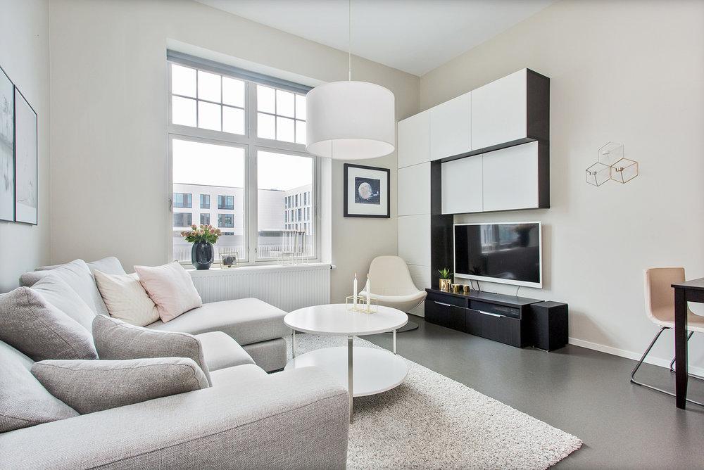Store vinduer gir rikelig med naturlig lys til leiligheten.