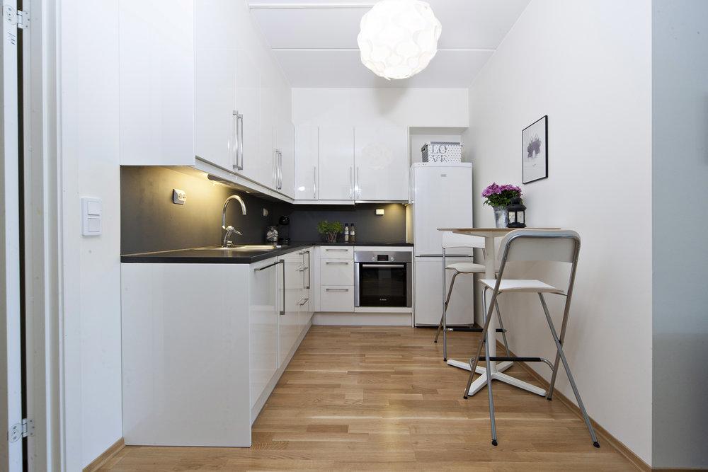 Lekkert kjøkken med innredning hvit høyglans utførelse.