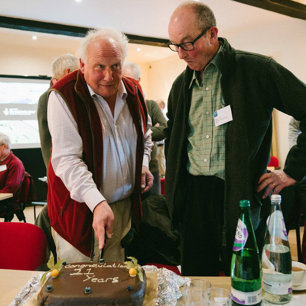Trustees Simon and Richard cutting the birthday cake