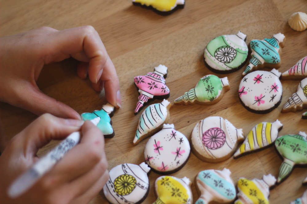 "I use an edible FoodWriter marker to draw on the cookies after using a food coloring ""watercolor"" wash"