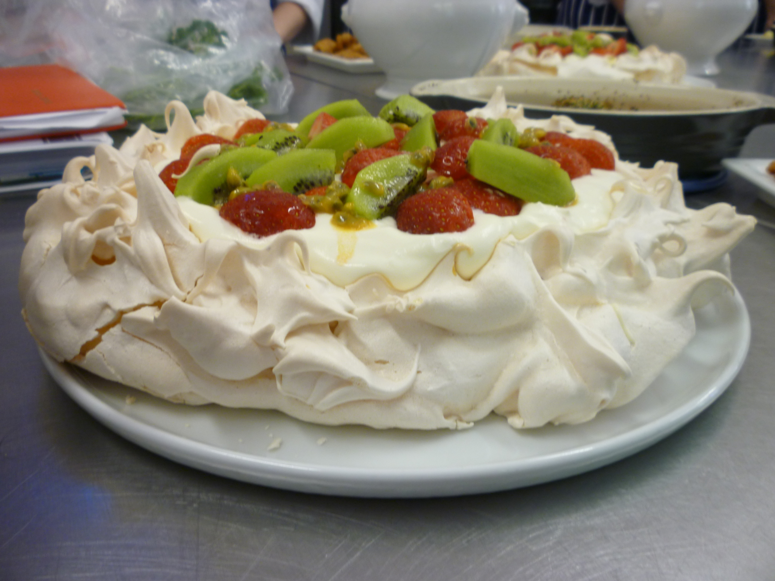 A pavlova with strawberries, kiwi and passion fruit.