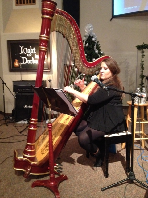Kristin playing the harp at church service