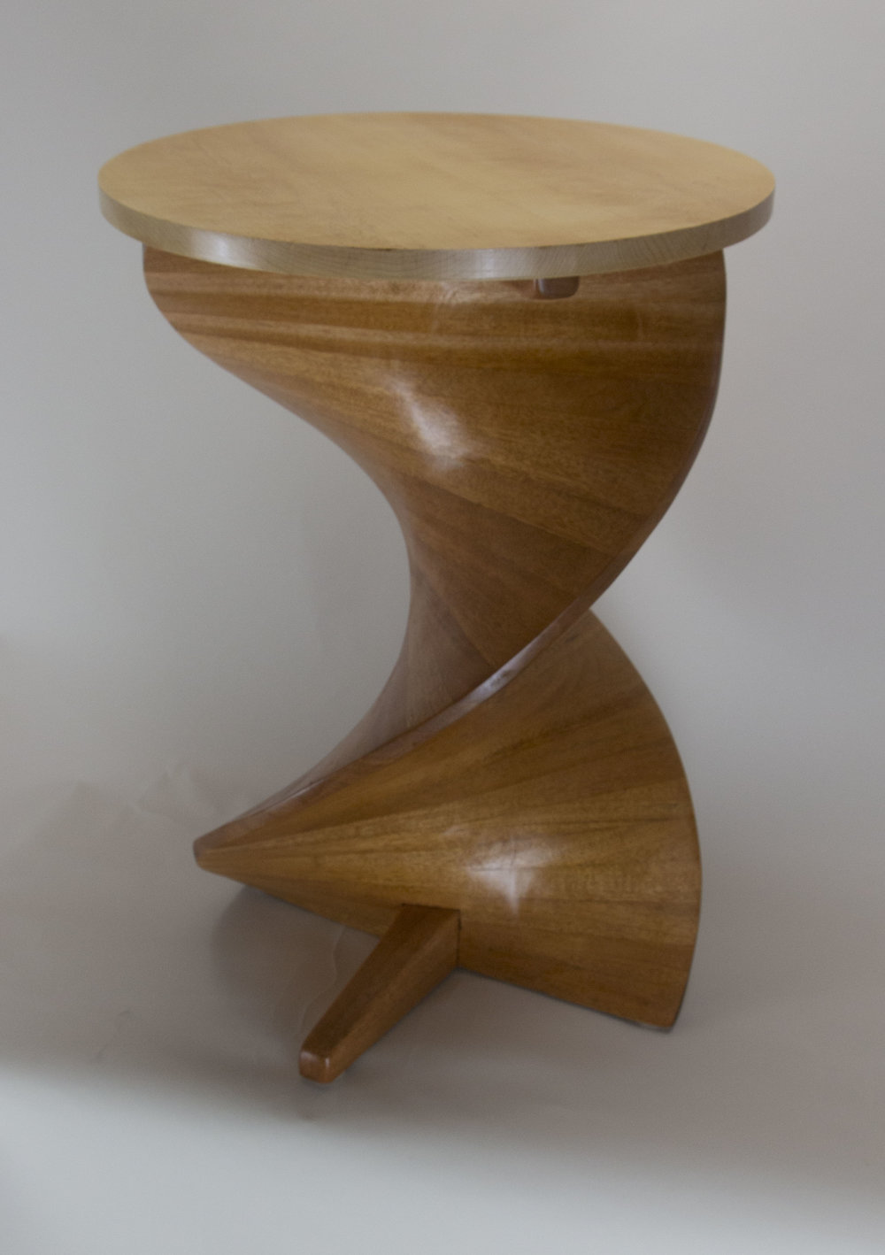 JIM OLESON - Helical Cocktail TableJim Oleson designs and makes furniture and sculptural objects that emphasize curved forms, using a wide variety of techniques to achieve these forms. His background in mathematics, physics, and medicine informs the entire design process from mechanical considerations to inclusion of shapes inspired by nature.