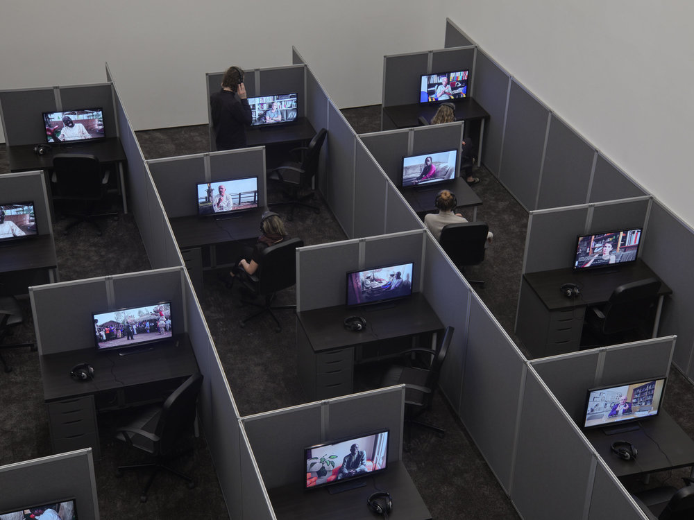 Kader Attia; Reason's Oxymorons, 2015; Installation; 18 films, cubicles, screens, office chairs, and desks, carpet, speakers, headphones; Reason's Oxymorons exhibition view at Lehmann Maupin, New York, 2017; Courtesy the artist, The Collection of The Hood Museum of Art at Dartmouth College, and Lehmann Maupin; Photo: Max Yawney.