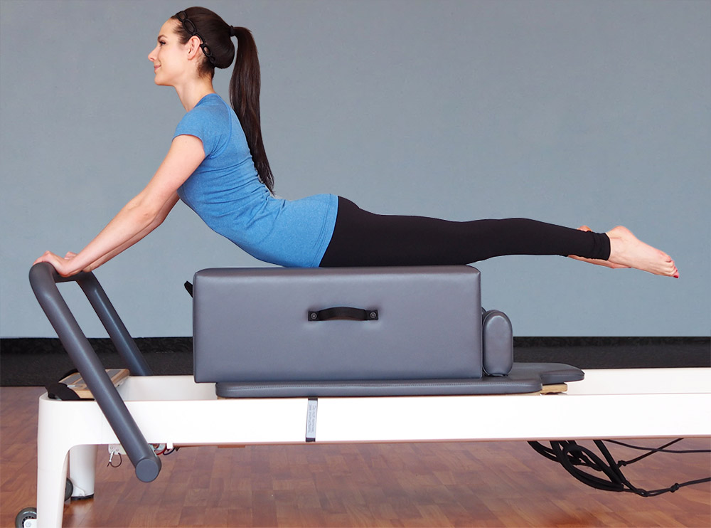 Client performing an exercise on a Pilates reformer