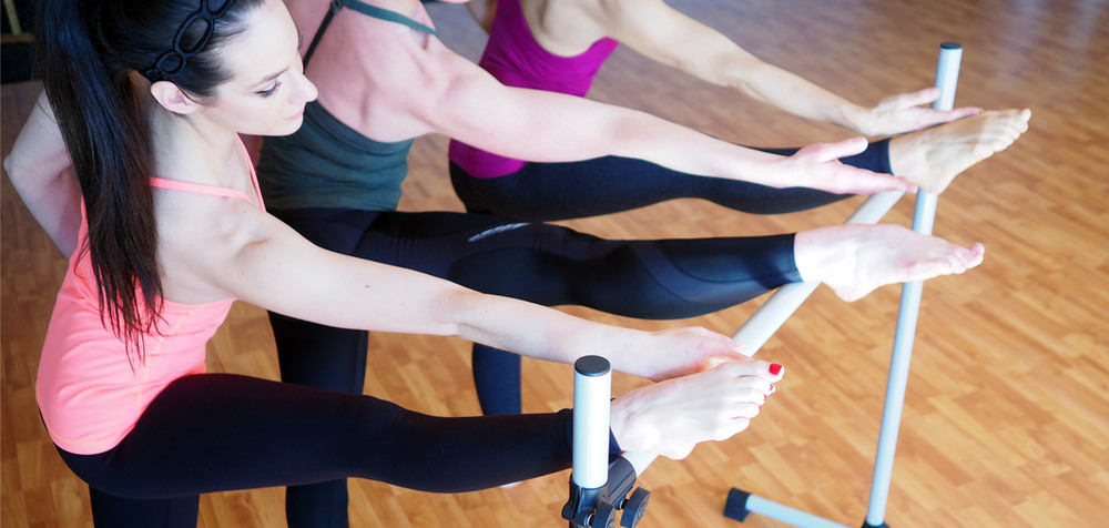 Three clients at an Intelligent Barre class