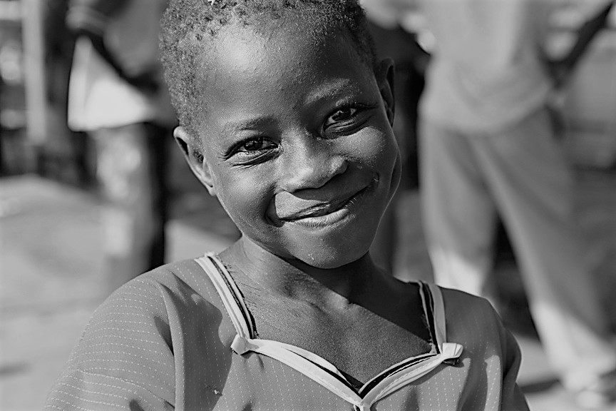 Young_girl_smiles_after_arriving_in_Juba,_Sudan BW.jpg