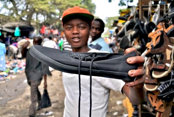 A young man in Nairobi receives a gently used pair of American shoes.
