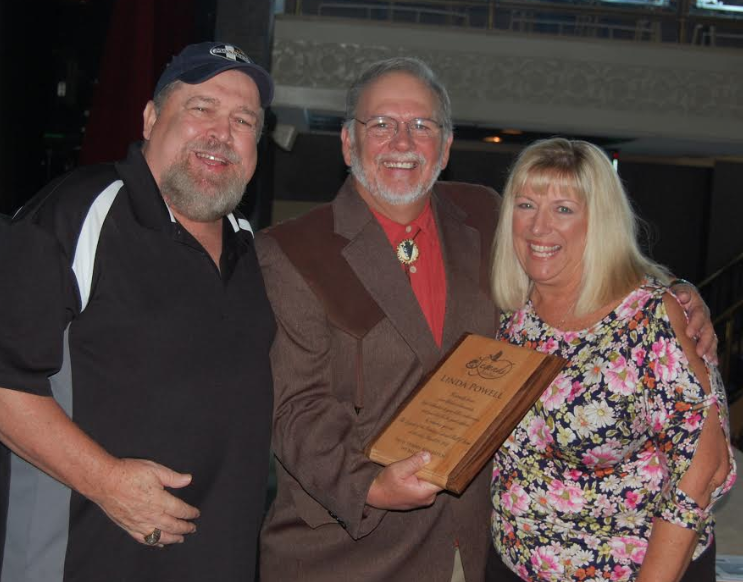 Linda Powell, pictured on the right, receives her Hall of Fame plaque from Garry Mason, center, and Ray Eye, left.