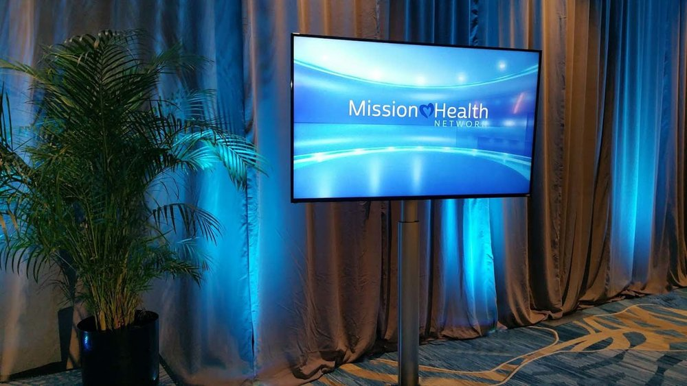 LCD Flat Panel TV on Floor Stand with 2 Audio PA Speakers. Setup in Hotel Conference Room for Business Event in Orlando