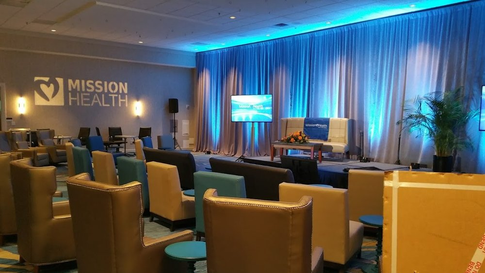 Pipe & Drape, Uplighting & Plants - Enhance any room, at any venue location with beautiful, eye-catching uplighting, staging, pipe & drape, plants, spotlight or stage lighting! Add a theme or your company colors bringing your entire event together visually!