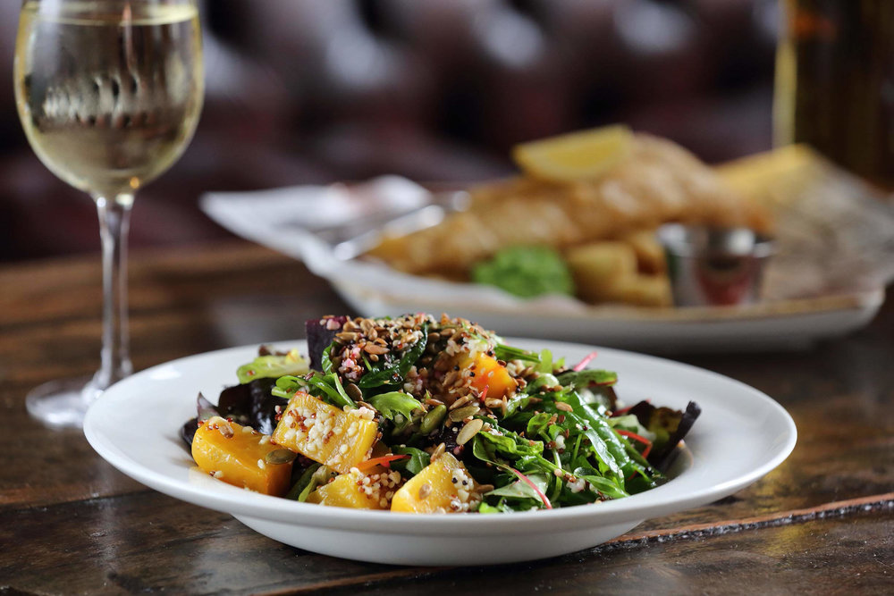 A plate of salad and a glass of wine, at the North Star pub, Ealing
