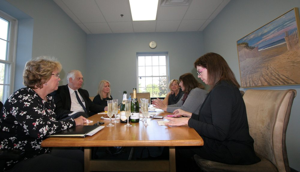 Reboli lawyer Laurie Vetere awaits the transfer of money to complete the purchase of 64 Main Street, Stony Brook. Joining her around the table (L to R) are Carolyn Slawski, Assemblyman Steve Englebright, Lois Reboli, Colleen Hanson, and BJ Intini.