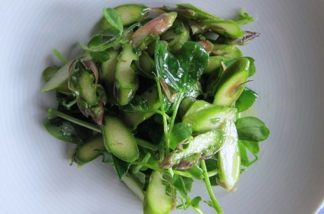 Raw Asparagus Salad    Photo ©Evie Saffron Strands         We collected the first cut of English Asparagus from our Kent Grower last week and, despite a return to lacklustre weather, the English season is definitely under way.  Here is a recipe, inspired by our friends at 40 Maltby Street, celebrating the early spears which are delicious eaten raw.  It also makes a few spears go a long way.        Raw Asparagus Salad   (Serves 4 as a starter)   8-12 asparagus spears A handful of pea-shoots  A few mint leaves 1 tbsp lemon juice 4 tbsp extra virgin olive oil Salt & pepper  Snap the tough ends off the asparagus.  Cut a diagonal slice off the bottom of each spear then slice them thinly.  Add salt and pepper to the lemon juice and mix.  Whisk in the olive oil to emulsify.  Toss the sliced asparagus and the pea shoots in the dressing.  Pile onto plates and serve.  (Add a few curls or a grating of Italian Parmesan or English Berkswell cheese if you like).