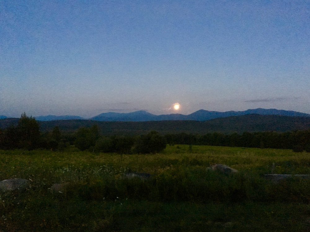The full moon rising with the high peaks on the horizon
