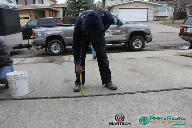 Measure gaps, ridges and joints in the concrete driveway.