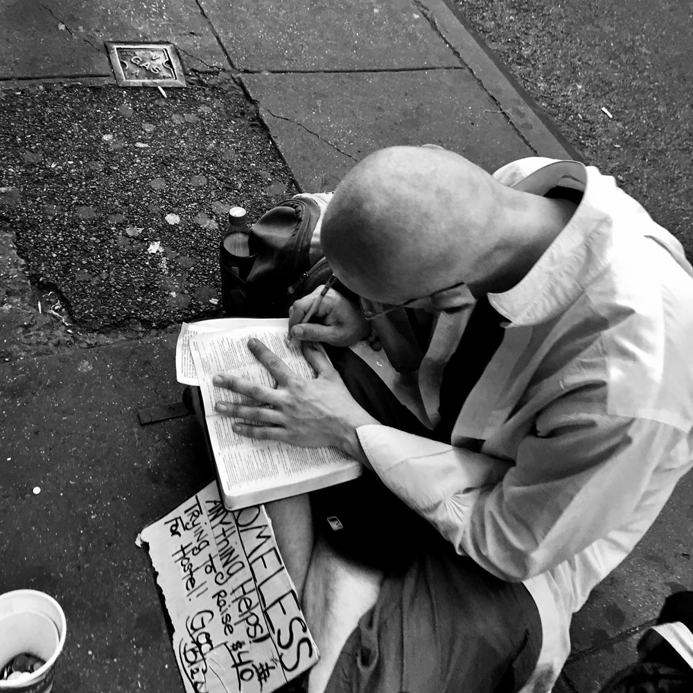 homeless man writing.jpg