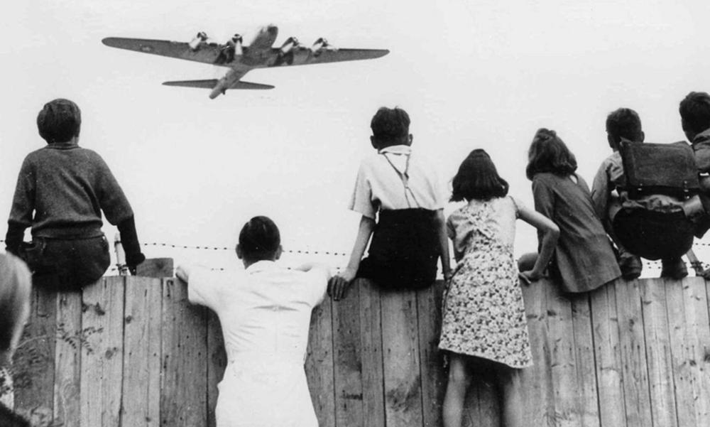 Västtyska barn tittar på ett amerikanskt plan med förnödenheter som flyger in mot Tempelhof under den Sovjetiska blockaden.Foto: Associated Press.