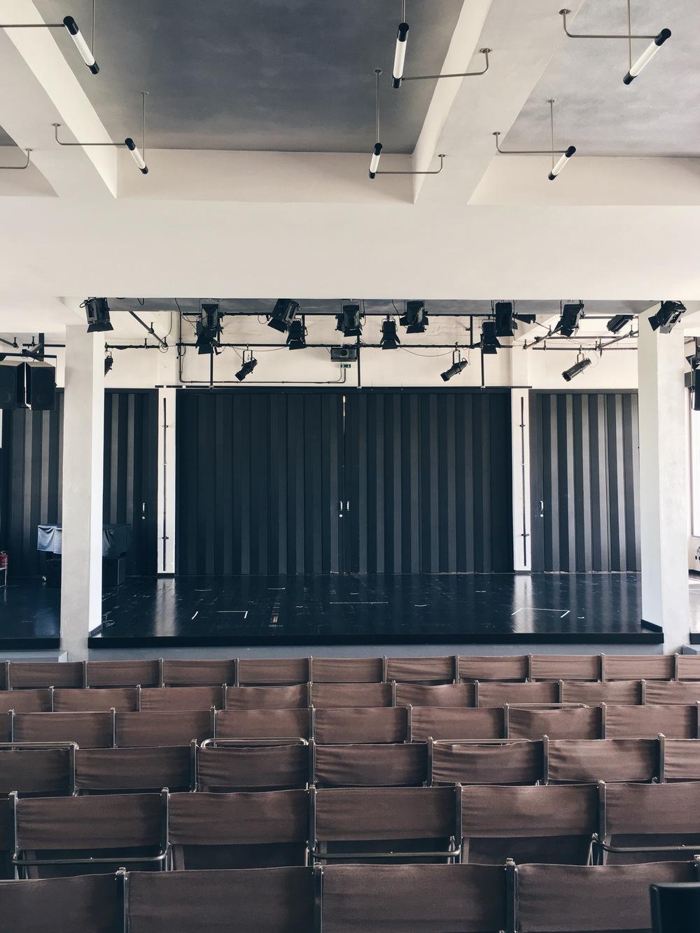 Auditoriet i Bauhausskolan, sommaren 2016. Bakväggen kan öppnas helt, där bakom ligger cafeterian. I taket hänger Max Krajewskis lampor, som binder ihop trapphuset med auditoriet.