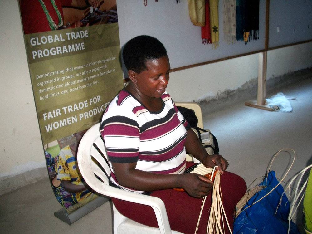 Nakayiza weaving a basket from banana fibers.