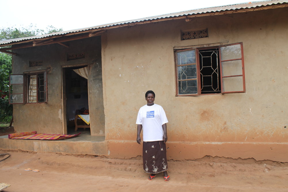 Nakayiza in front of her renovated home.
