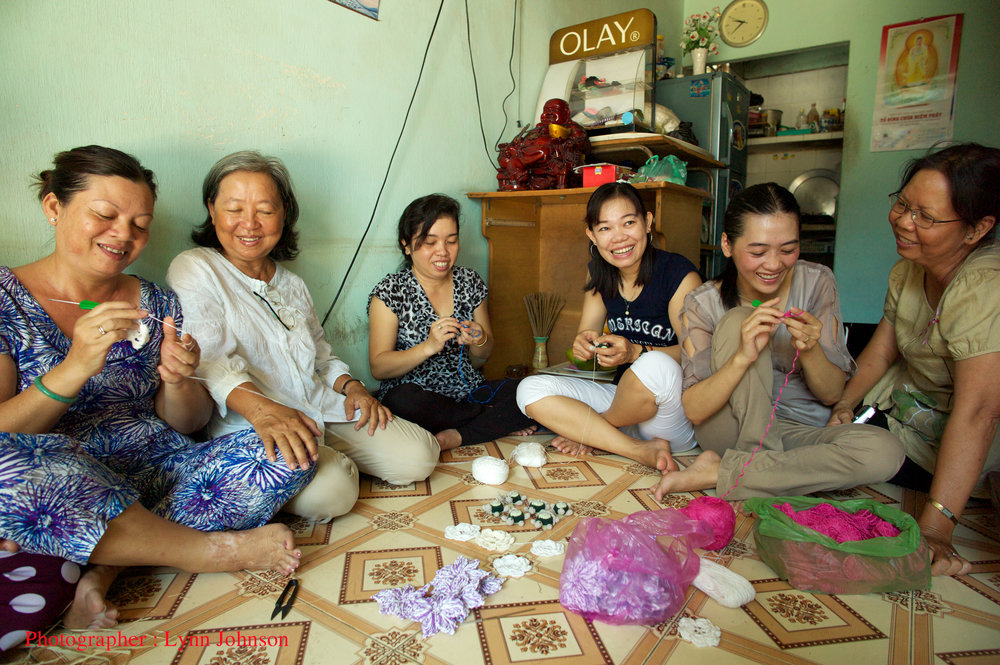 Le Khanh (second from left) and My (far right), with women artisans who are earning a fair wage through their crochet work in Vietnam.