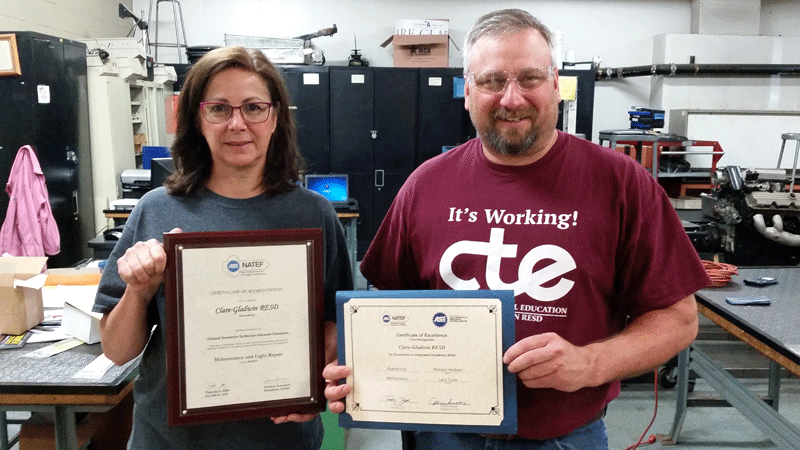 Clare-Gladwin CTE Auto Tech Paraeducator Suzanne Ledford and Instructor Rich Hollister display the NATEF certification documents.