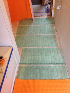 Warmly Yours floor heat installed. Now dry fitting Ditra. (Orange layer) on top