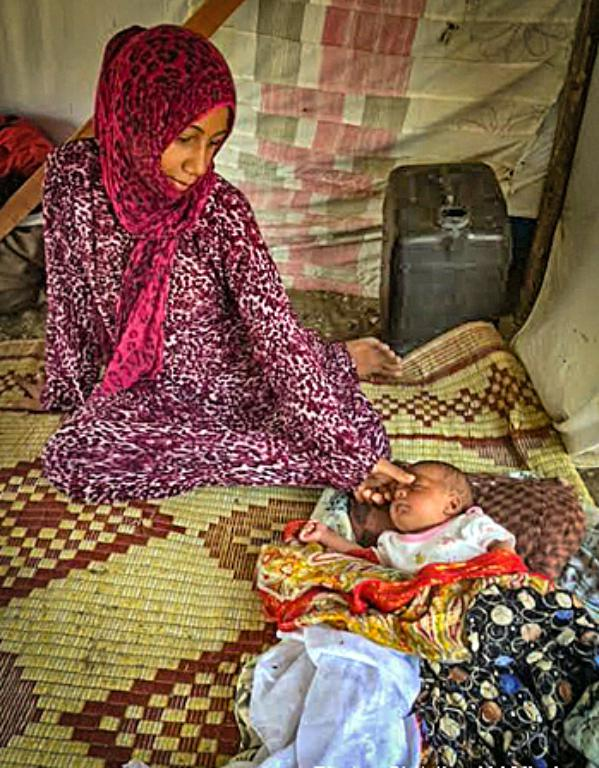 Syrian refugee woman and child from Aleppo, Syria at a makeshift tent camp in Turkey ( Christian Aid Mission )