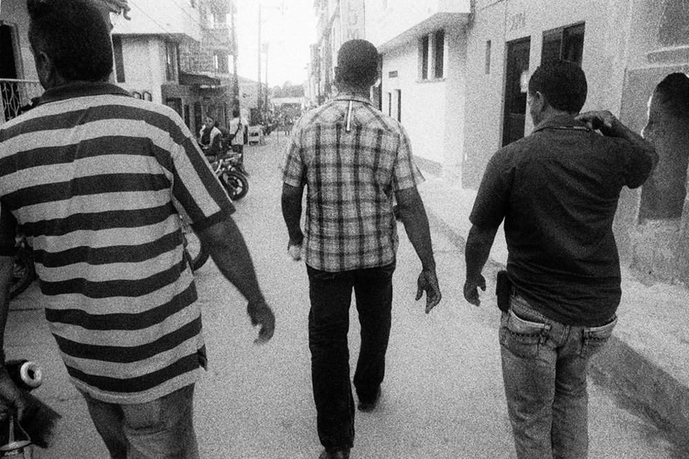 Mr. Dairo Rúa (center), at the time president of the Segovia section of the Sintraminergética miners union, flanked by bodyguards as he walks towards his home in Segovia, Antioquia. Like other leaders of the miners union, Mr. Rúa has been subject to numerous death threats, which he believes come form paramilitary groups opposed to the union's activity on behalf on the rights of mine workers.
