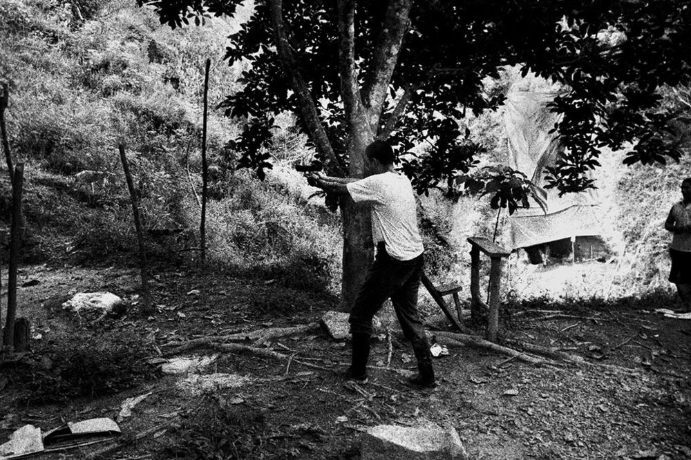 Bodyguard of Dairo Rúa practices firing his pistol in secluded area of Segovia, Antioquia. Like other leaders of the miners union, Mr. Dairo Rúa at the time president of the Segovia section of the Sintraminergética miners union, has been subject to numerous death threats, which he believes come form paramilitary groups opposed to the union's activity on behalf on the rights of mine workers.