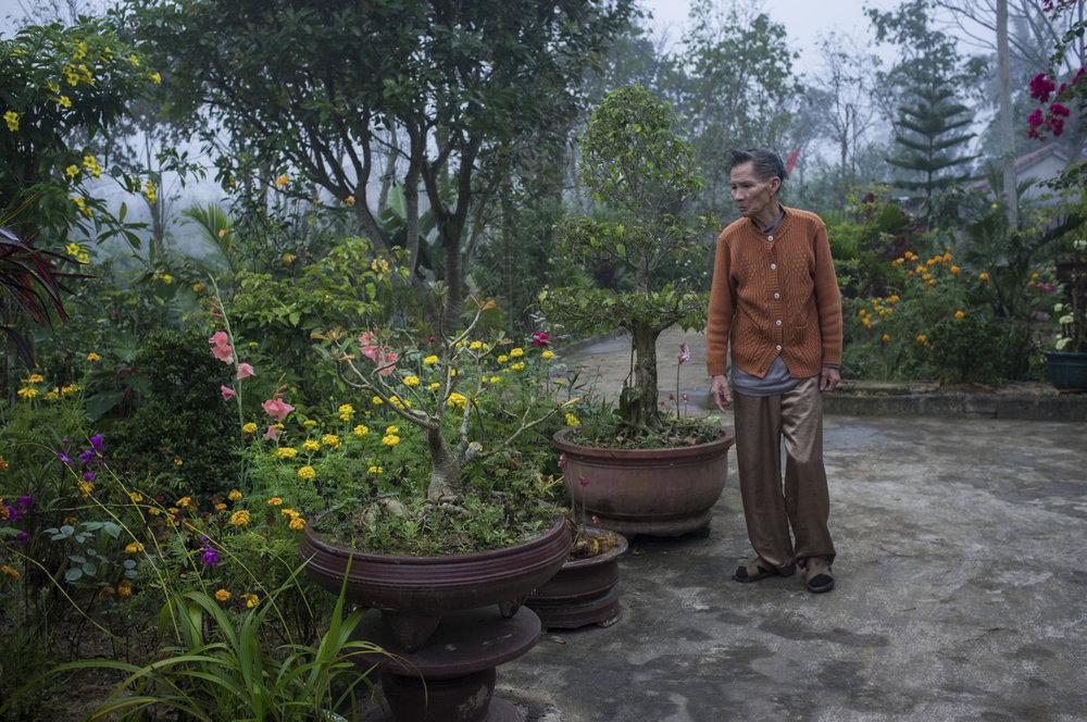 Hoang Van Sy walking in his garden. © Tran Quoc Ahn