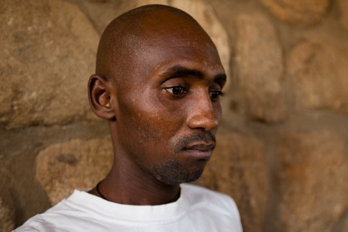 Sani Umaru, 44, stared vacantly into space most of the time. His voice had been reduced to an almost inaudible mumble. He arrived at the Yola Federal Medical Centre in late October. Both of his hands were wrapped in thick bandages due to gunshot wounds so severe that they say his left hand will have to be amputated. He remembers Boko Haram men making him lie down in a road-side gutter with five other men, just before the execution style shooting. He was a farmer from Madagali town before the attack and the only survivor of the shooting. 2014, © Rahima Gambo