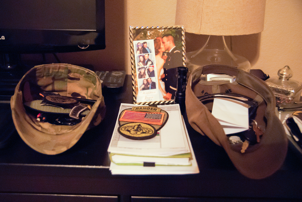 Army Ranger hats and badges on nightstand next to wedding photo.