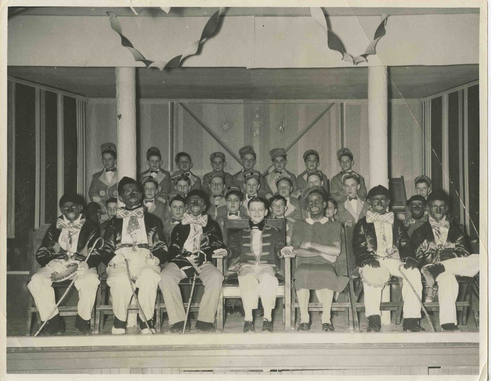 """Montreal catholic school minstrel show  My father, Leo Julien, as the Interlocutor in his anglophone Montreal Catholic school minstrel show. He told me he was twelve years old in the 8' X 12"""" black-and-white picture. He was born in April 1928, so this is probably 1940/41.No other identifying information except for a rubber stamp on the back:""""""""Photo by Cyril Cassidy."""" My father ended up estranged from much of his large Irish-French family in later years, and so spoke of his youth haltingly, with gaps. I know that he did live off rue Clark at this time, near Parc Jarry and the Jean Talon Market. My father always said about this picture, ironically, that he never met a black African-Canadian until a very young Oscar Peterson played his high school dance a few years later. My dad was a great social dancer, so he and Oscar had, in his words, """"hit it off"""".  Written by Martin Julien."""