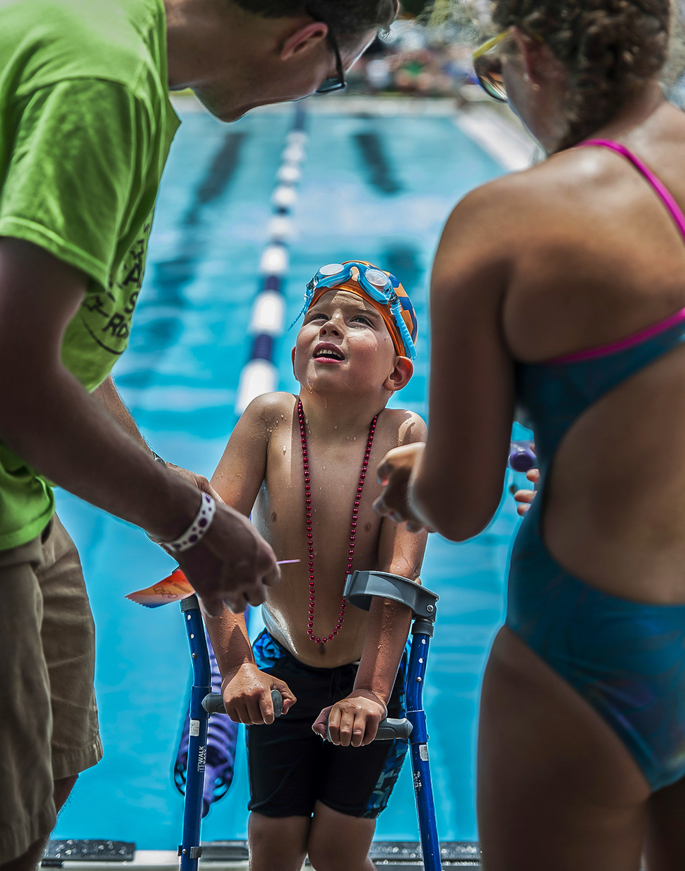 "Thomas Prechtel, 5, receives a participation ribbon after swimming the 25 meter freestyle during the Southern Indiana Swim Association meet at South Harrison State Park in Elizabeth, Ind., on Saturday, July 13, 2013. He is diagnosed with Spina Bifida, which renders him unable to use his legs. This is his first summer swimming and isapart of the Jeffersonville Aquatic swim team. His mother said that ""it makes him feel free when he is floating the water."""