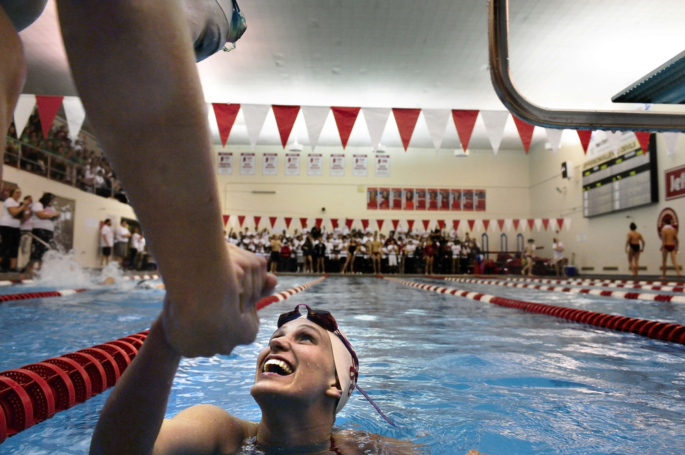 Red Devil swimmer Rachel Walker is congratulated by her 200 meter relay team after realizing they set a pool record by 0:00.53 of a second during the annual Jeffersonville vs. Floyd Central swim meet held at the Jeffersonville aquatic center on Dec. 18 2014. The Red Devils would end up winning the meet.